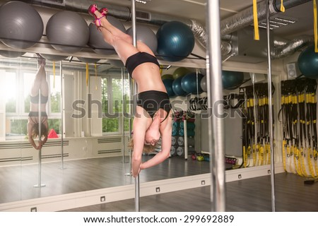 Pole dancer performing closed bridge - stock photo
