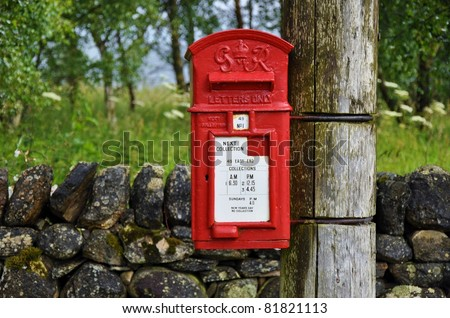 Pole mounted english mailbox in the countryside - stock photo