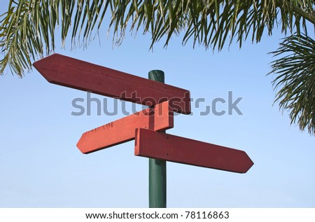 Pole of three directional signs in redwood under a palm leaf and blue sky as background