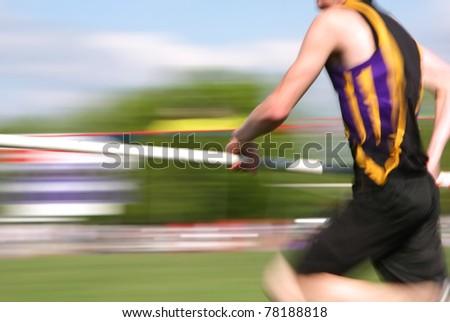 Pole vaulter running down the runway (motion blur) - stock photo