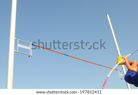 Pole vaulting. An Athlete in the middle of the vaulting phase during an athletic competition. - stock photo