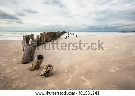 Poles on the beach in Tversted in Denmark - stock photo