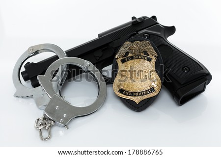 Police badge, gun and handcuffs on white background - stock photo