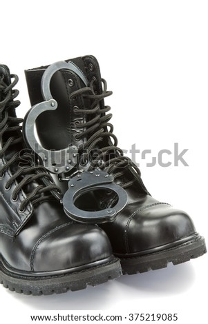 Police boots and handcuffs - equipment and aids or fetish - stock photo