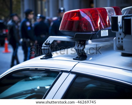 Police car lights close up. A group of policemen on the background. - stock photo