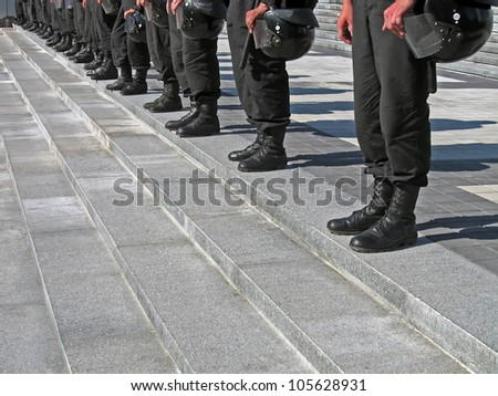 police cordon in black uniform with hard hat (helmet) on the stone staircase, security details - stock photo
