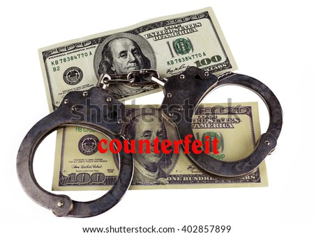 police handcuffs false and real hundred-dollar bill. the concept of counterfeiting of money and punishment. - stock photo