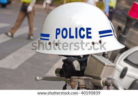 Police helmet on motorcycle handlebars with traffic cops in the background - stock photo