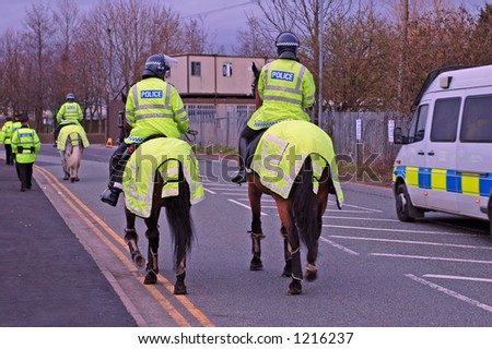 Police Horses and riders with other police officers in the background. - stock photo