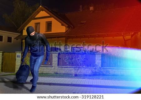 Police lights and runaway masked burglar with balaclava and black bag. - stock photo