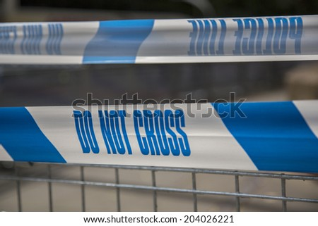 police line do not cross caution tape on metal railing fence - stock photo