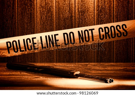 Police line do not cross safety warning tape at forensic murder crime scene with shotgun weapon shooting evidence on floor during a criminal law justice investigation in rough grunge sepia - stock photo