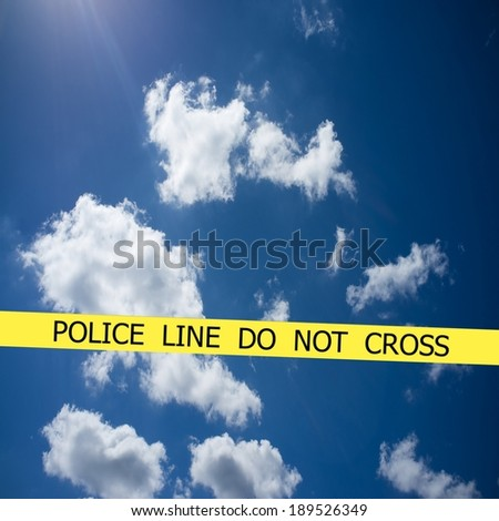 Police line do not cross sign tape on blue cloudy sky background - stock photo