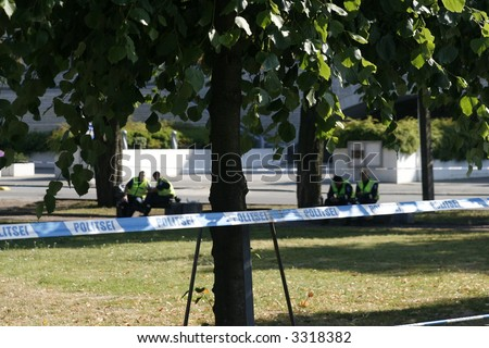 police line restricting an area, inside of it policemen are sitting and guarding - stock photo
