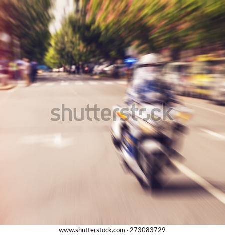 Police motorcycle racing through city streets. Radial blurred zoom with vintage instagram look added in post processing - stock photo