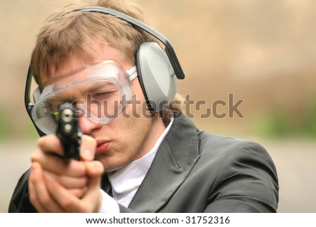 police officer aiming with gun into the camera - stock photo