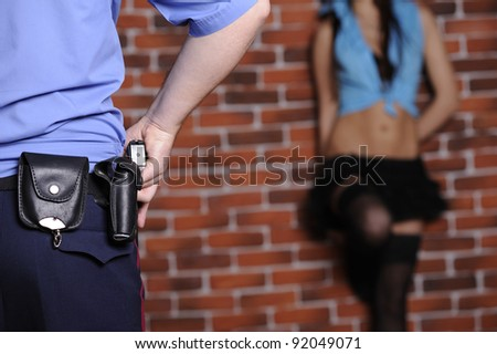 Police officer delay prostitute in front of  brick wall - stock photo