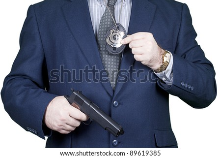 Police officer holding a gun and a badge - stock photo