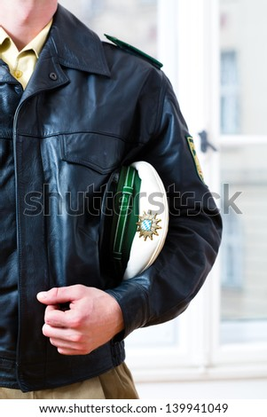 Police officer in police station, wearing his uniform with leather jacket and hat, he is ready for operation - stock photo