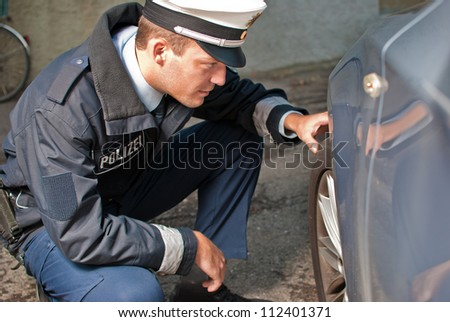 Police officer is checking a tire of a vehicle - stock photo