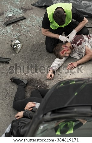 Police officer is checking state of car crash victims - stock photo