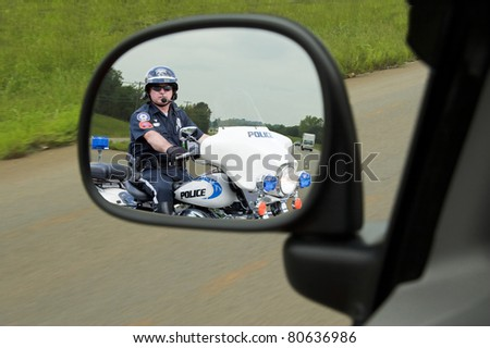 Police officer on his motorcycle watching for speeders is pulling in behind fast moving vehicle - stock photo