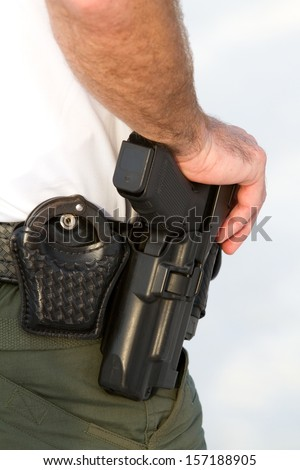 Police officer rests his hand on his weapon belt which also holds his handcuffs. - stock photo