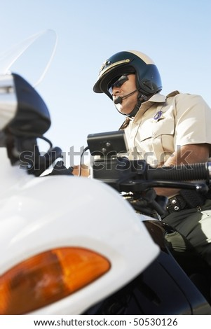 Police officer sitting on motorcycle, low angle view, (low angle view) - stock photo