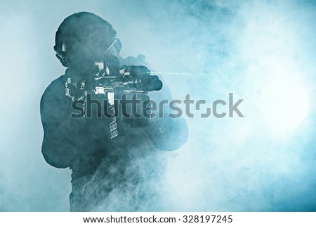 Police officer SWAT in black uniform in the smoke studio shot - stock photo