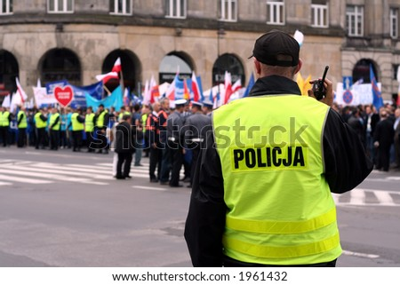 Police officer talking on a radio during an anti-government demonstration in Warsaw Poland on 7 Oct 2006 (Blue March by Platforma Obywatelska). Purposely taken with a shallow DOF not to detail faces. - stock photo
