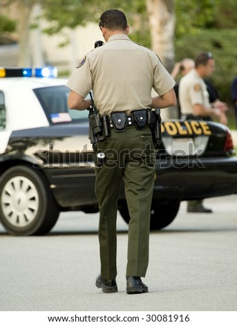 Police officer walking toward his car - stock photo