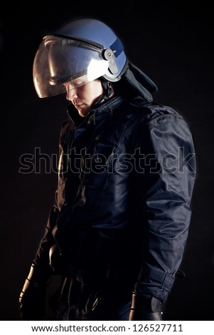 Police officer wearing protective uniform as protection from protesters - stock photo
