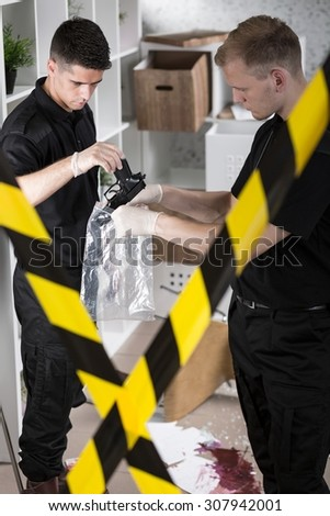 Police officers collecting evidences of the crime - stock photo
