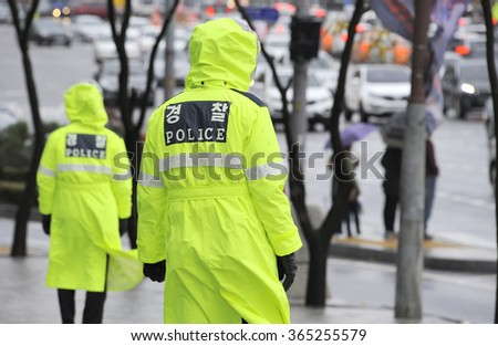 Police officers in the rain at a street in Seoul, South Korea - stock photo