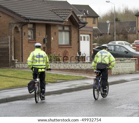 Police Officers on Bicycles patrol the streets - stock photo