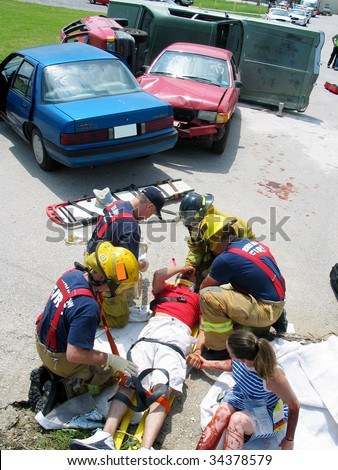 Police officers tend to car crash victims in a staged accident for training purposes - stock photo