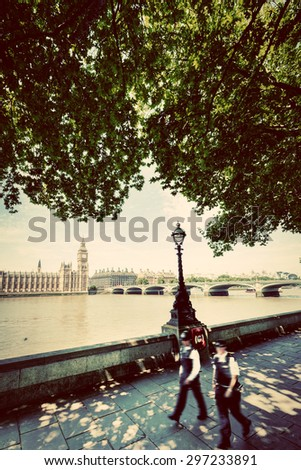 Police officers walk opposite to Big Ben, Westminster Bridge and River Thames in London, England, UK. English symbols. Vintage style - stock photo