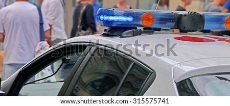 Police patrol car during a patrol in control city crowded with people - stock photo