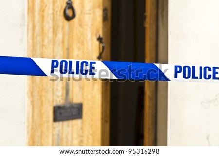 Police tape strung across an open front door with shallow depth of field