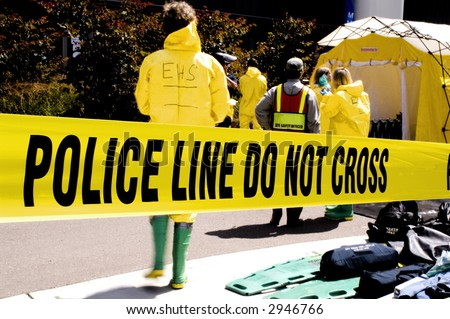 Police Tape with safety/Hazmat workers in the background - stock photo