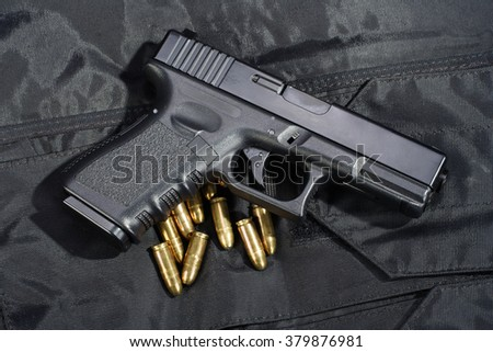 Police weapon and equipment on black uniform background  - stock photo
