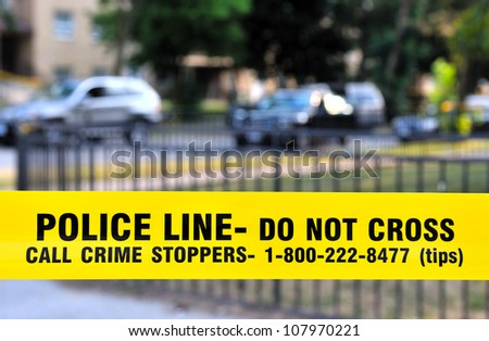 Police yellow  �POLICE LINE - Do not cross� tape (lower third) with fence and cars in the background