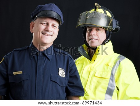 Policeman and fireman both photographed against a black background. - stock photo