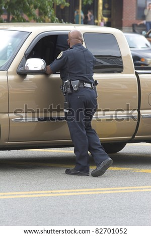 Policeman checking vehicles and watching crowds - stock photo