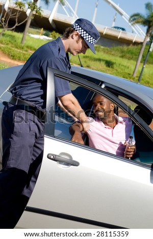 policeman pull out a drunk driver out of a car - stock photo