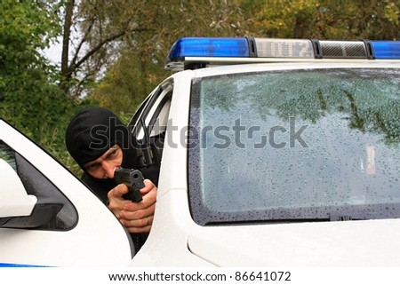 Policeman shoots from the police vehicle - stock photo