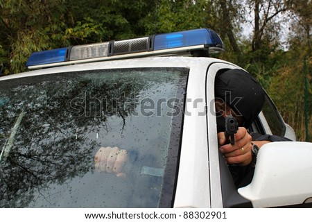 Policeman shoots from the police vehicle, detail, front view