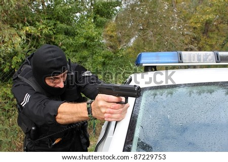 Policeman shoots next to the police vehicle, detail - stock photo