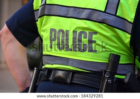 policeman wearing a neon safety vest - stock photo