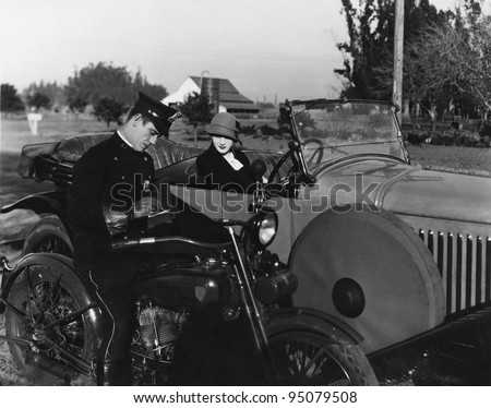 Policeman writing female driver ticket - stock photo